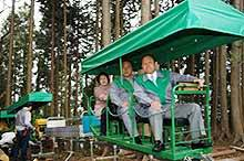 Happy Japanese businessmen ride the monorail up Mt. Honita